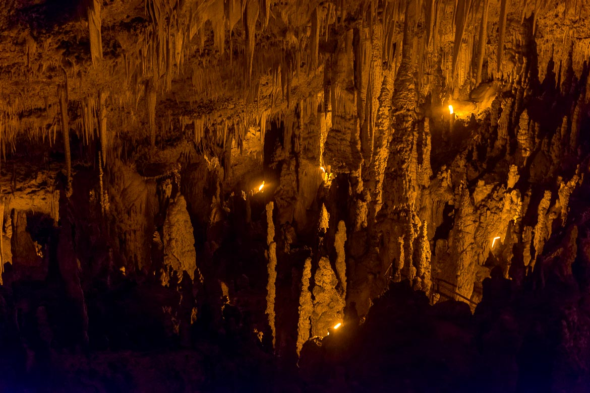 This photo was taken inside Perama Cave. It shows stalagmites and stalactites dimly lit.