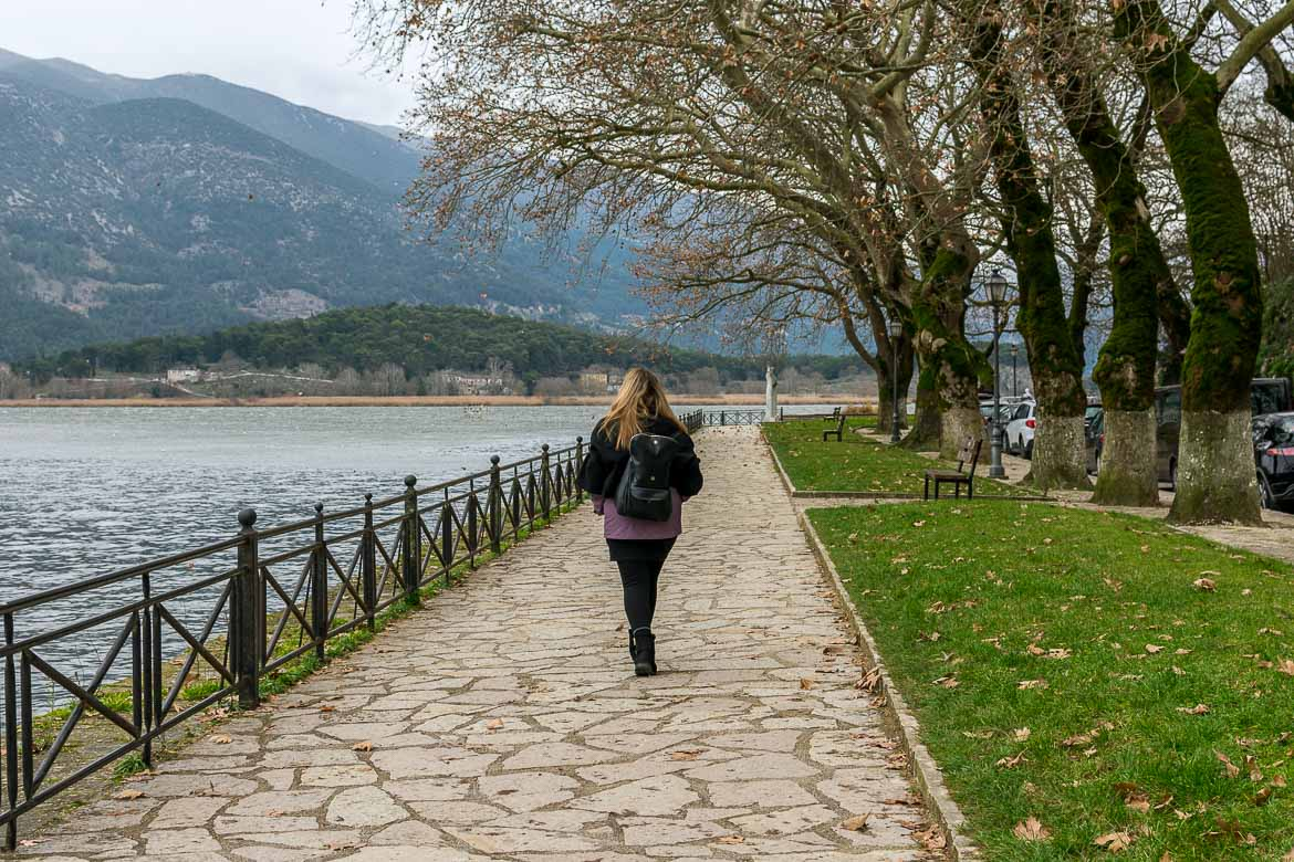 This is a photo of Maria walking along the lake on a cobblestone path.
