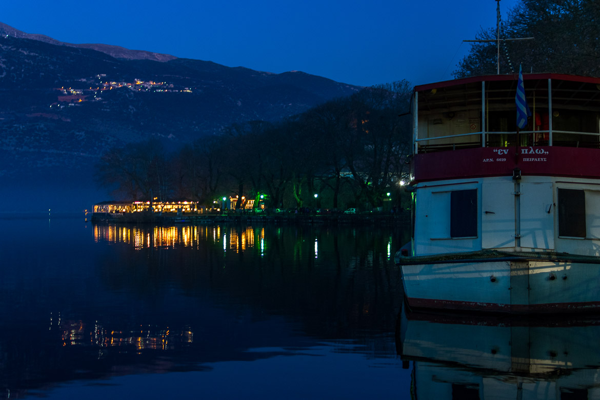 This image shows the lake of Ioannina in the evening. There are beautiful reflections on the tranquil waters.
