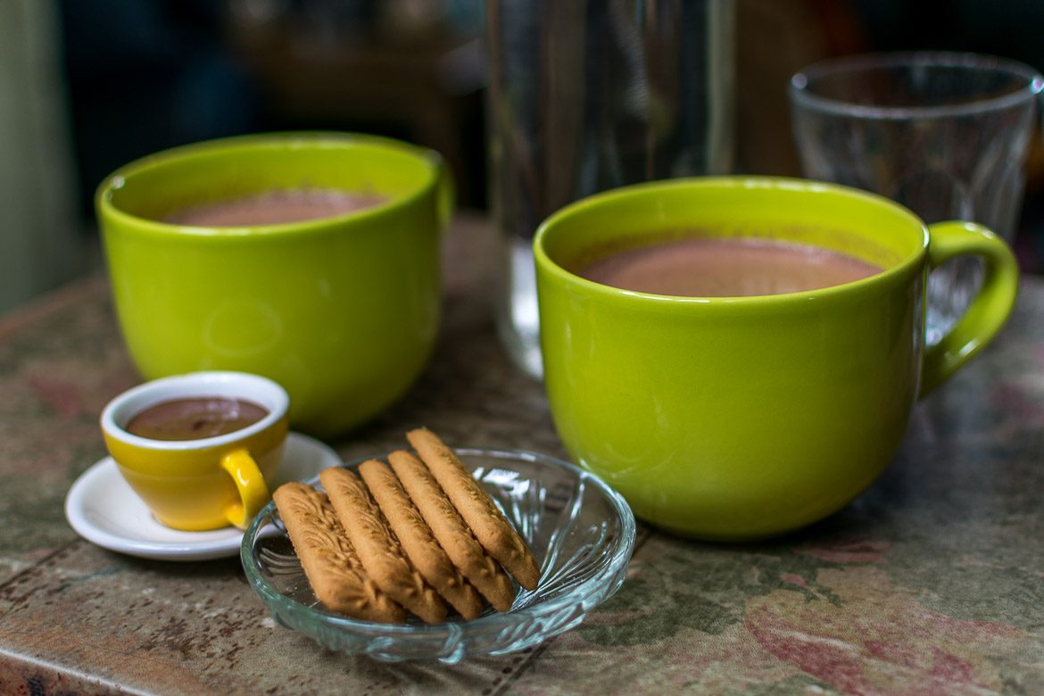 This image shows two green cups of hot chocolate accompanied by biscuits.