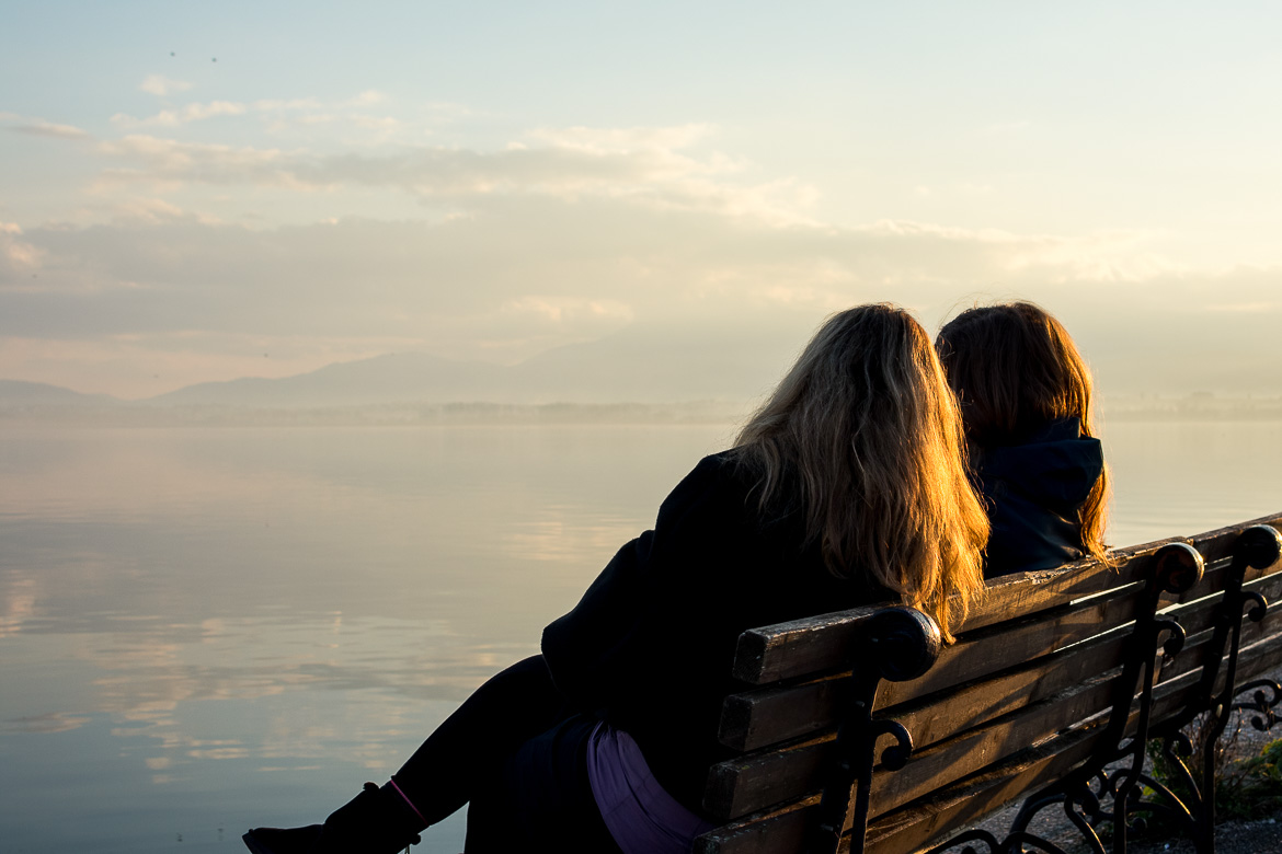 This is a photo of Maria and Katerina sitting on a bench admiring the view to the lake.