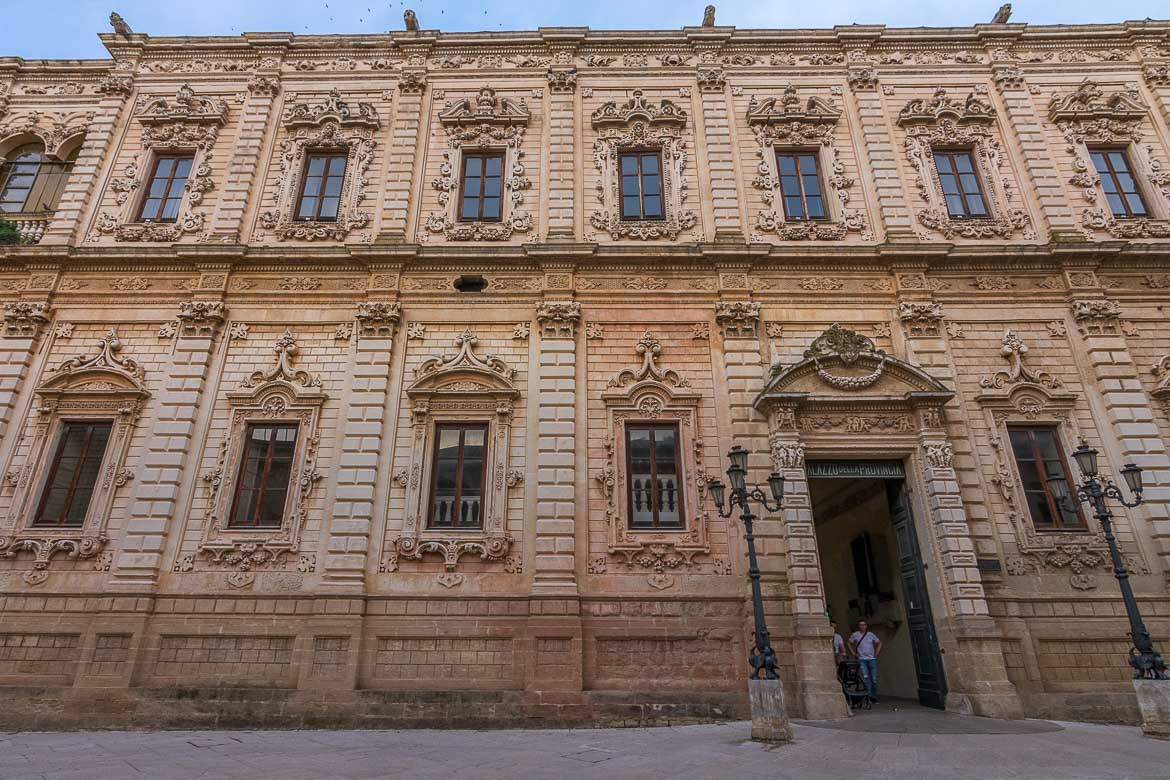 This photo shows a facade of a historical building in Lecce. There are elaborate details and it is a typical example of the barocco leccese architectural style.