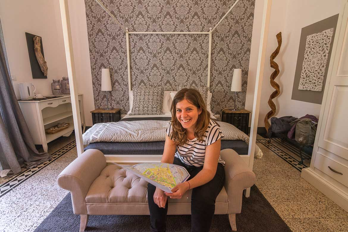 This is a photo of Katerina smiling at the camera with a map in her hand. She is sitting in front of a wonderful bed at one of the Junior Suites at Palazzo Bignami.