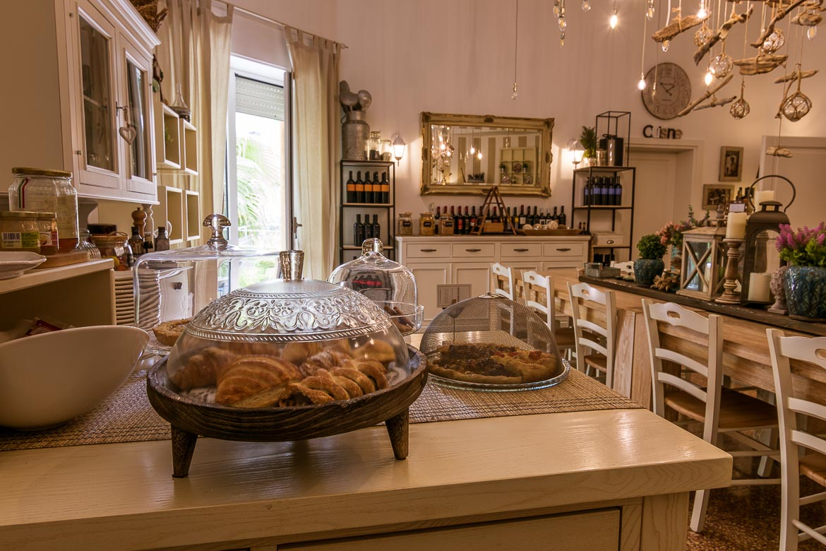 This photo shows the kitchen at Palazzo Bignami. In the foreground, platters with sweet and savoury treats. In the background, the cosy dining table with chairs and the wine collection.