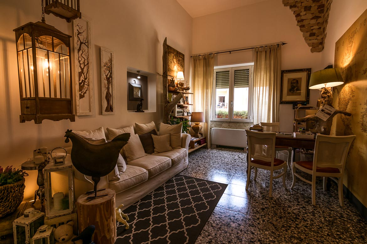 This photo shows the reception area at Palazzo Bignami. There is a cosy white sofa and a desk, warm lighting and french windows. The room is stylishly decorated.