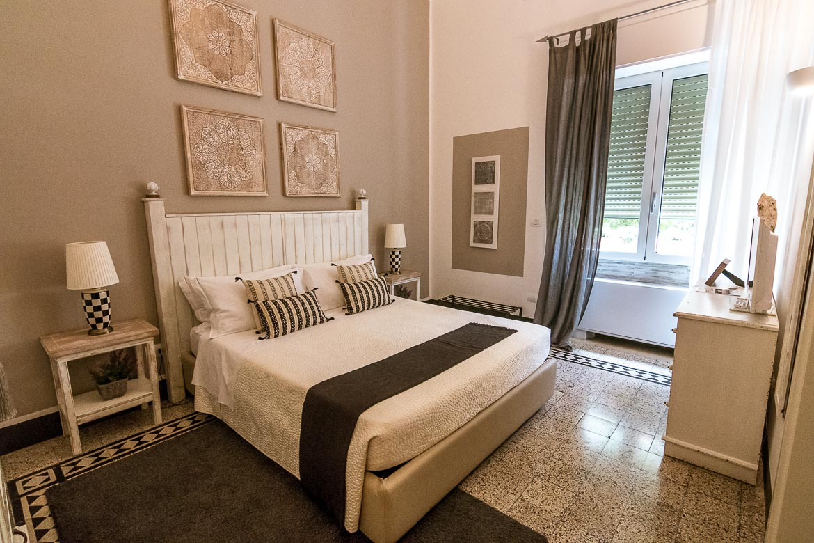 This is a photo of one of the rooms at Palazzo Bignami. The room is beautifully decorated in white and grey colours.