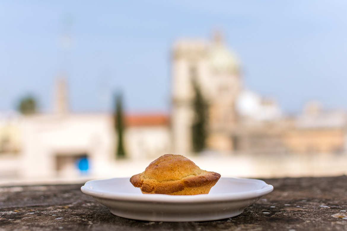 This is a close up of a pasticciotto leccese. In the background, Lecce's rooftops in a bokeh capture.