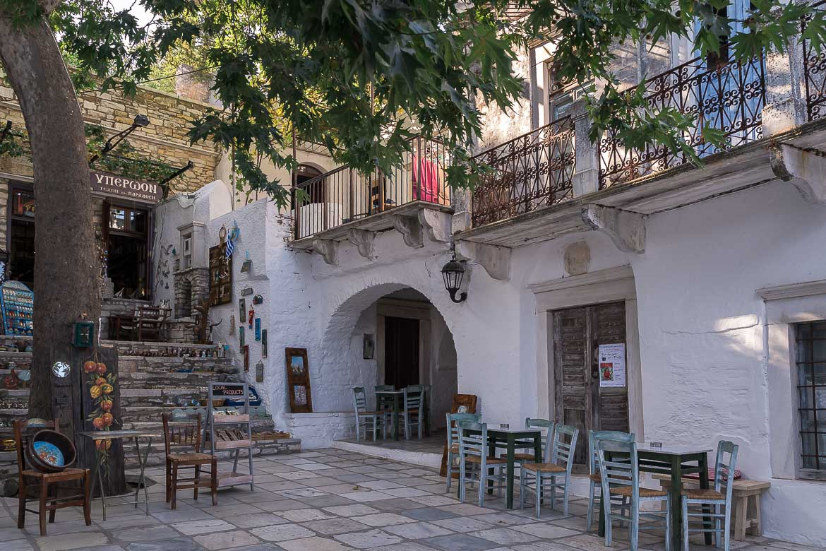 This image shows the main square in Apeiranthos. It's made of marble, there's an old plane tree in the middle and traditional chairs and tables everywhere. There's also a shop.