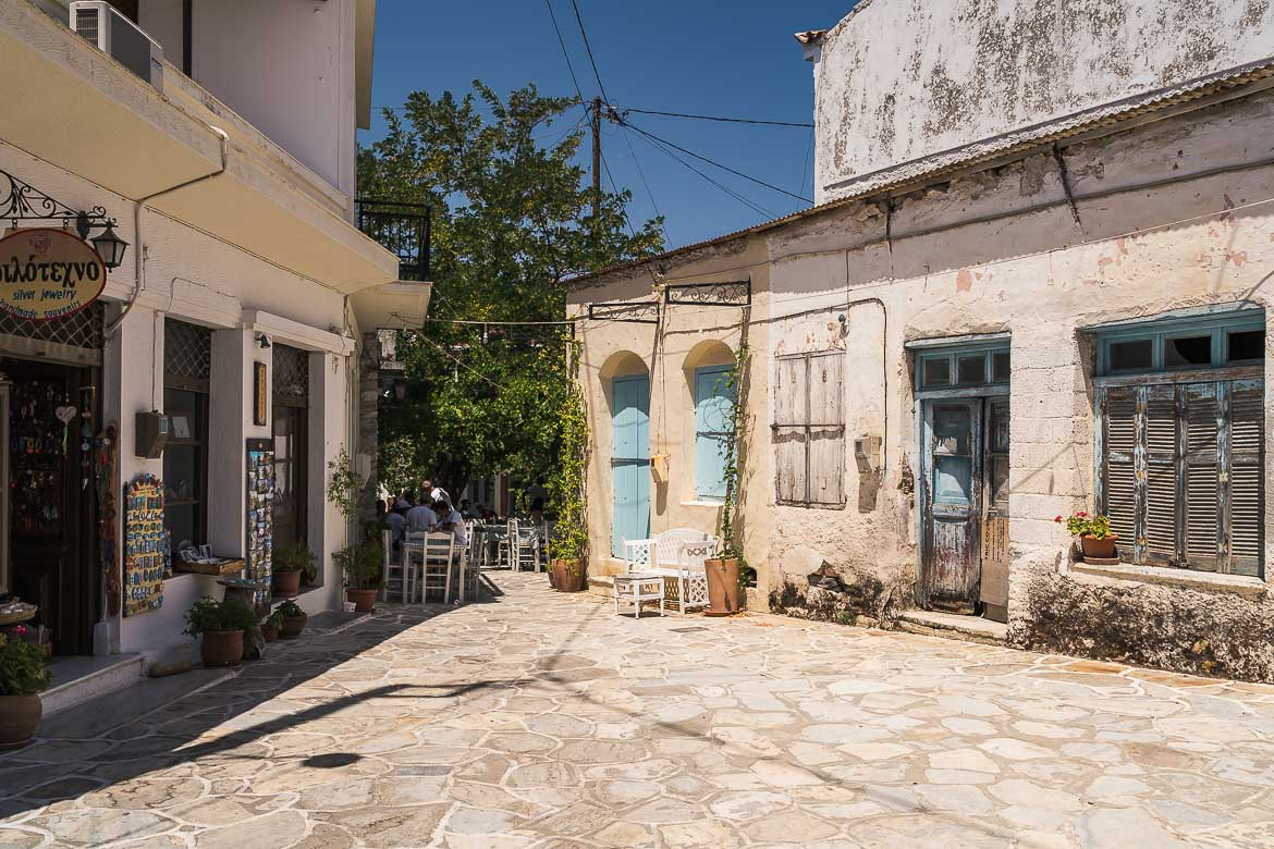 This image shows Chalki Naxos. There's an abandoned building in the foreground and a restaurant in the background.