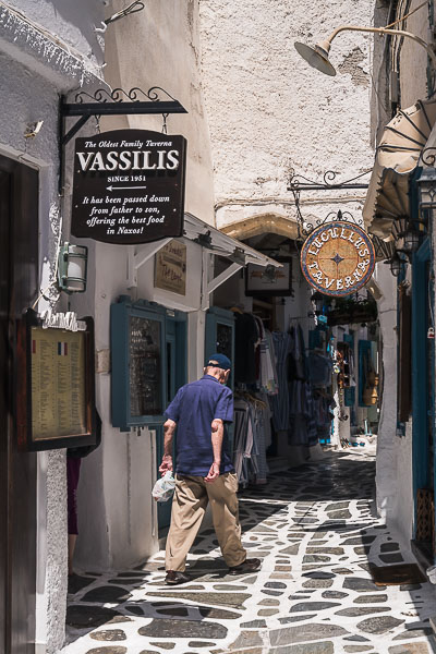 This image shows a man walking along an alley in the Old Market in Naxos Island Greece.