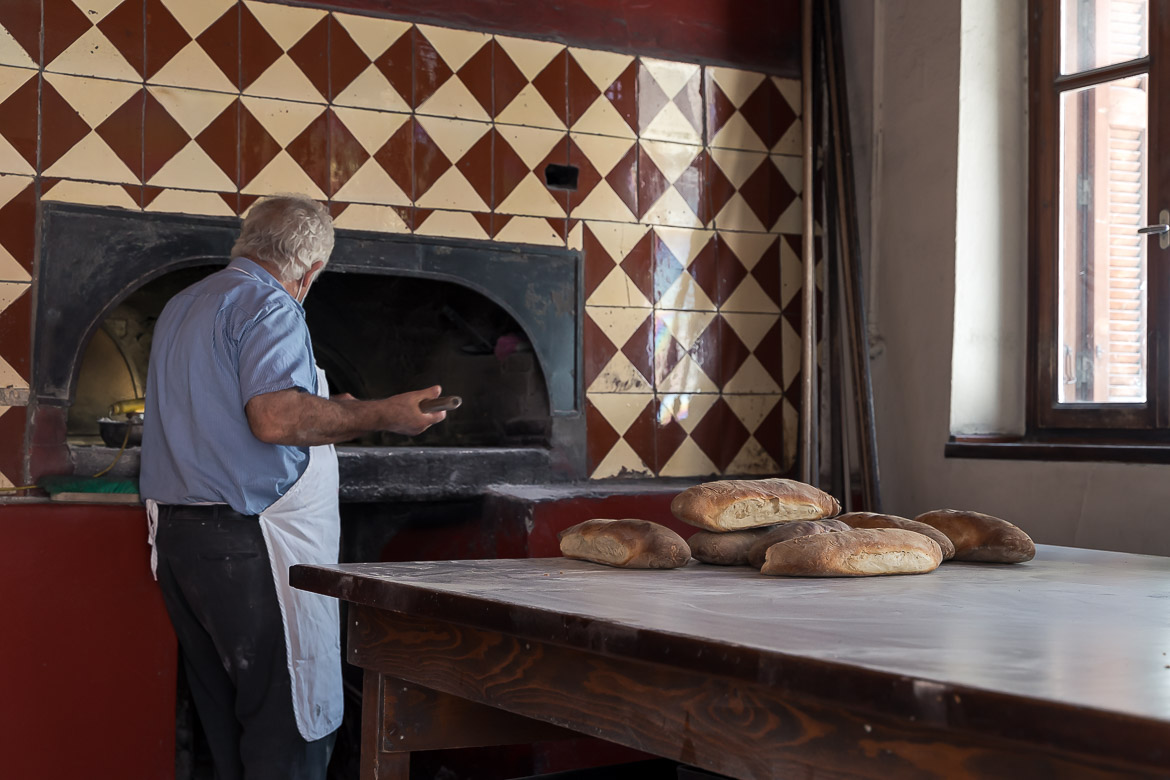 This image shows a baker taking out bread from the oven.
