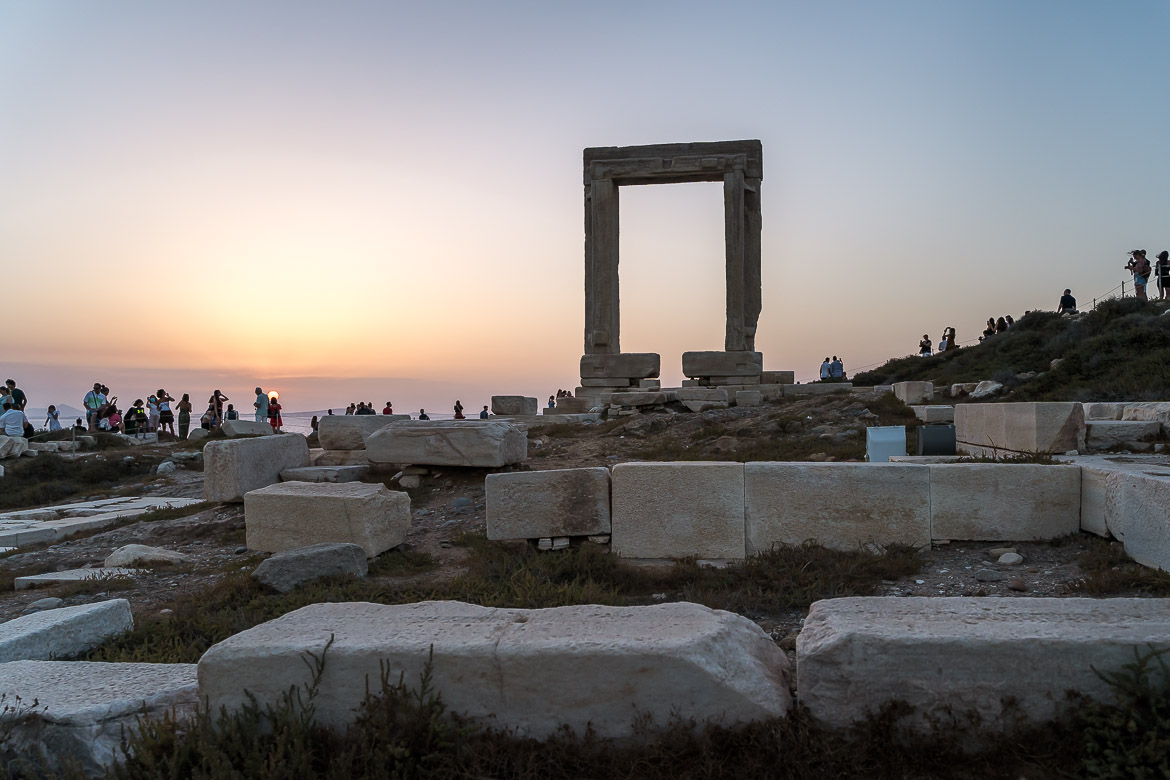 This image shows Portara and the crowds that gather there during sunset. The Greek Island of Naxos is at its best outside peak season.