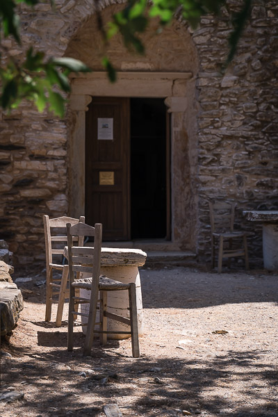 This image shows the courtyard of the monastery of Fotodotis. There are two chairs and a makeshift table.