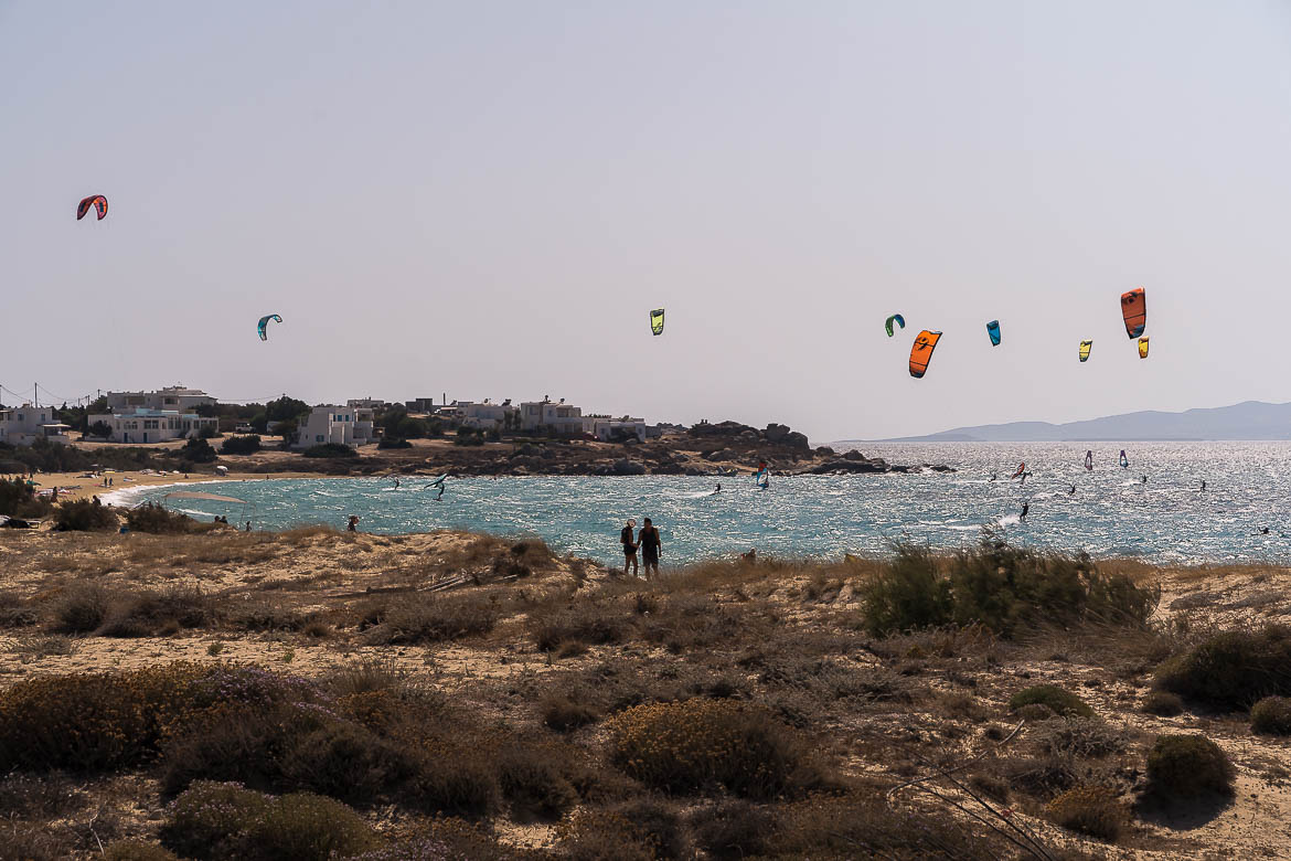 This image shows windsurfers and kitesurfers on Mikri Vigla beach on a windy day. Taming the wind is one of the best activities in Naxos.