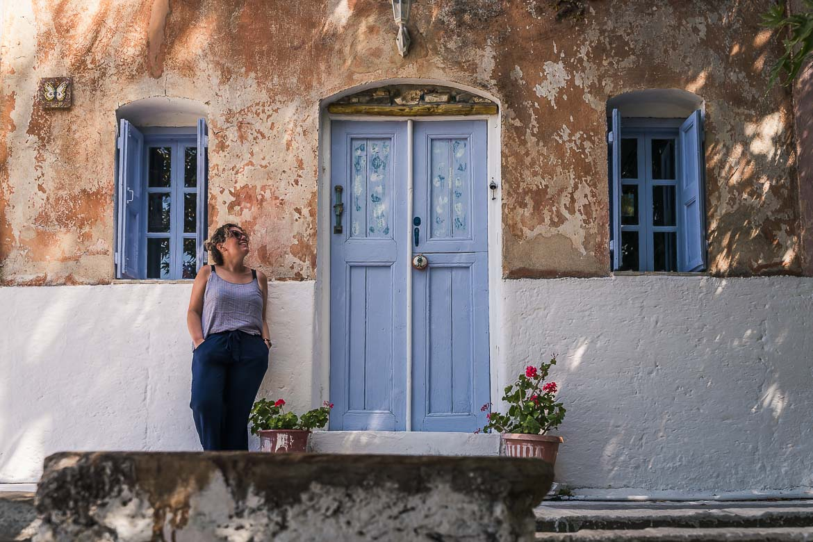 This image shows Maria standing at the door of the most picturesque cafe in Mili village.