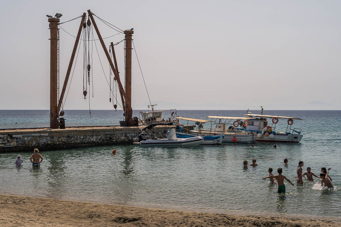 This image shows Moutsouna's port. Old facilities of the emery mines can be seen on the pier. In the foreground, chlidren play in the sea.