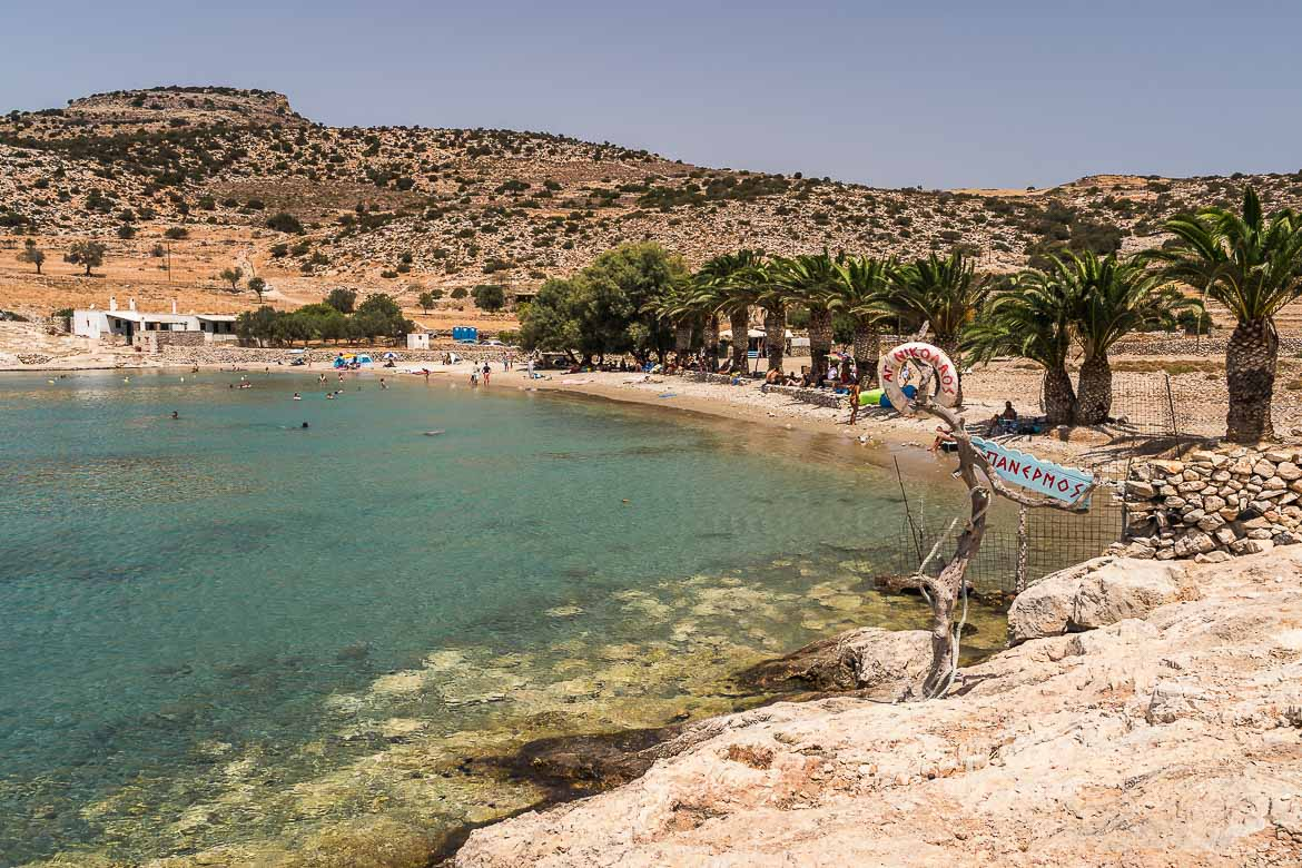 This image shows Panermos, one of the most exotic beaches of Naxos. Along the beach there is a line of palm trees.