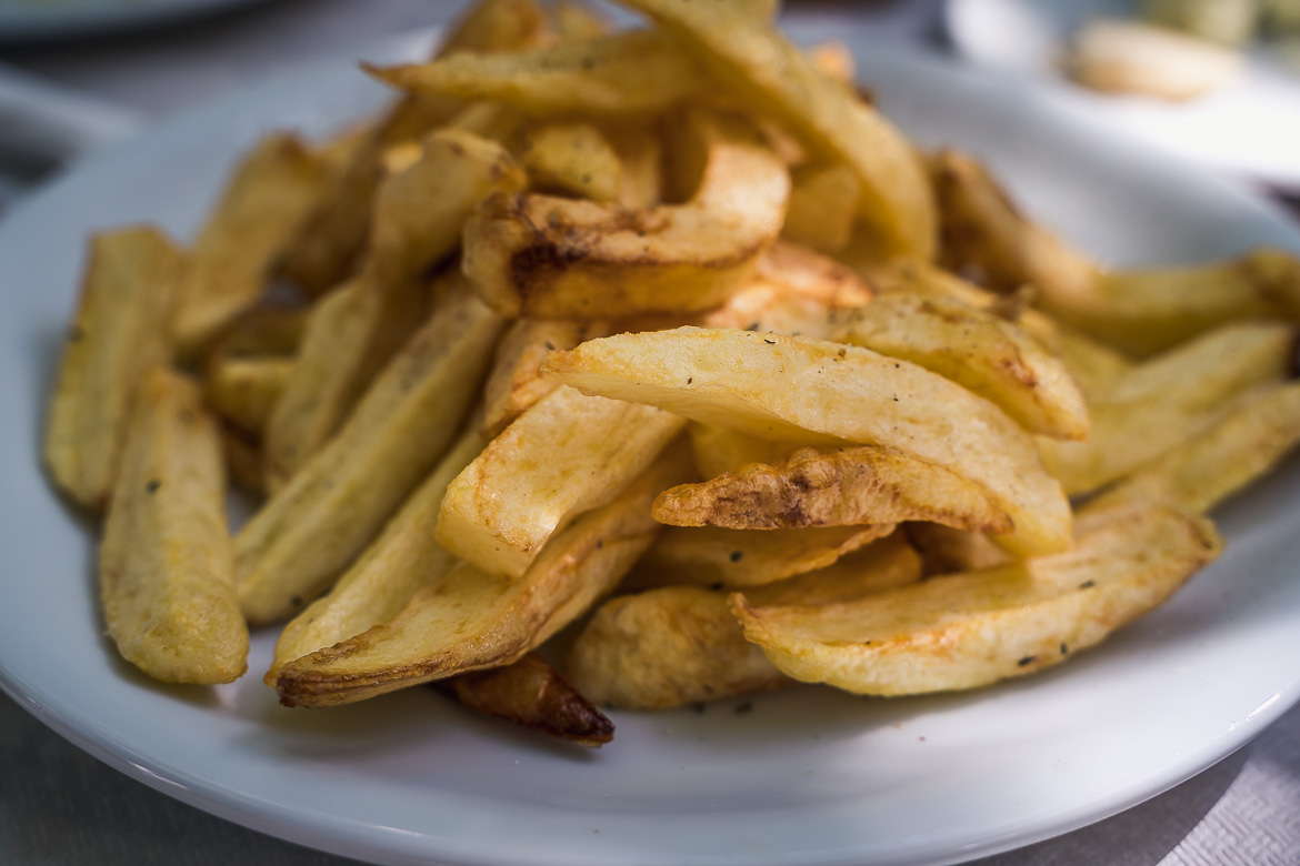 This image shows a portion of fried potatoes. Eating potatoes is one of the best things to do in Naxos.