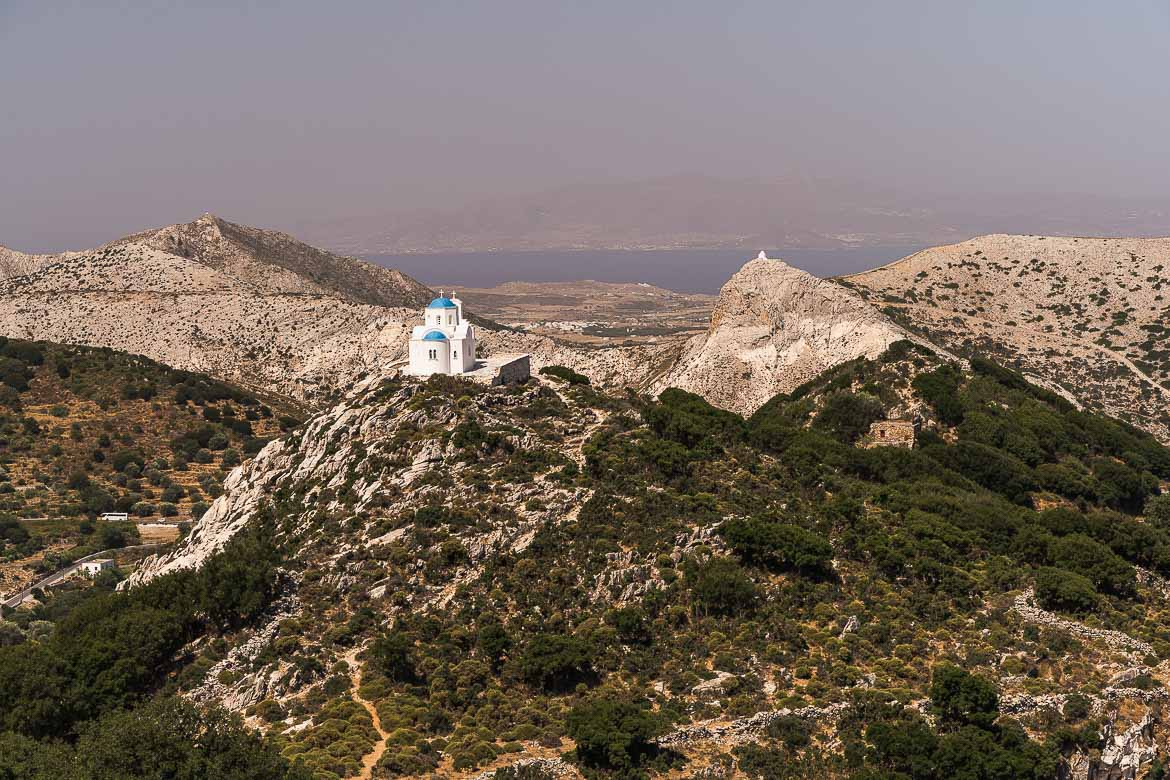 This image shows a panoramic view of Naxos landscape. There is a church in the foreground while Paros Island can be seen in the background.