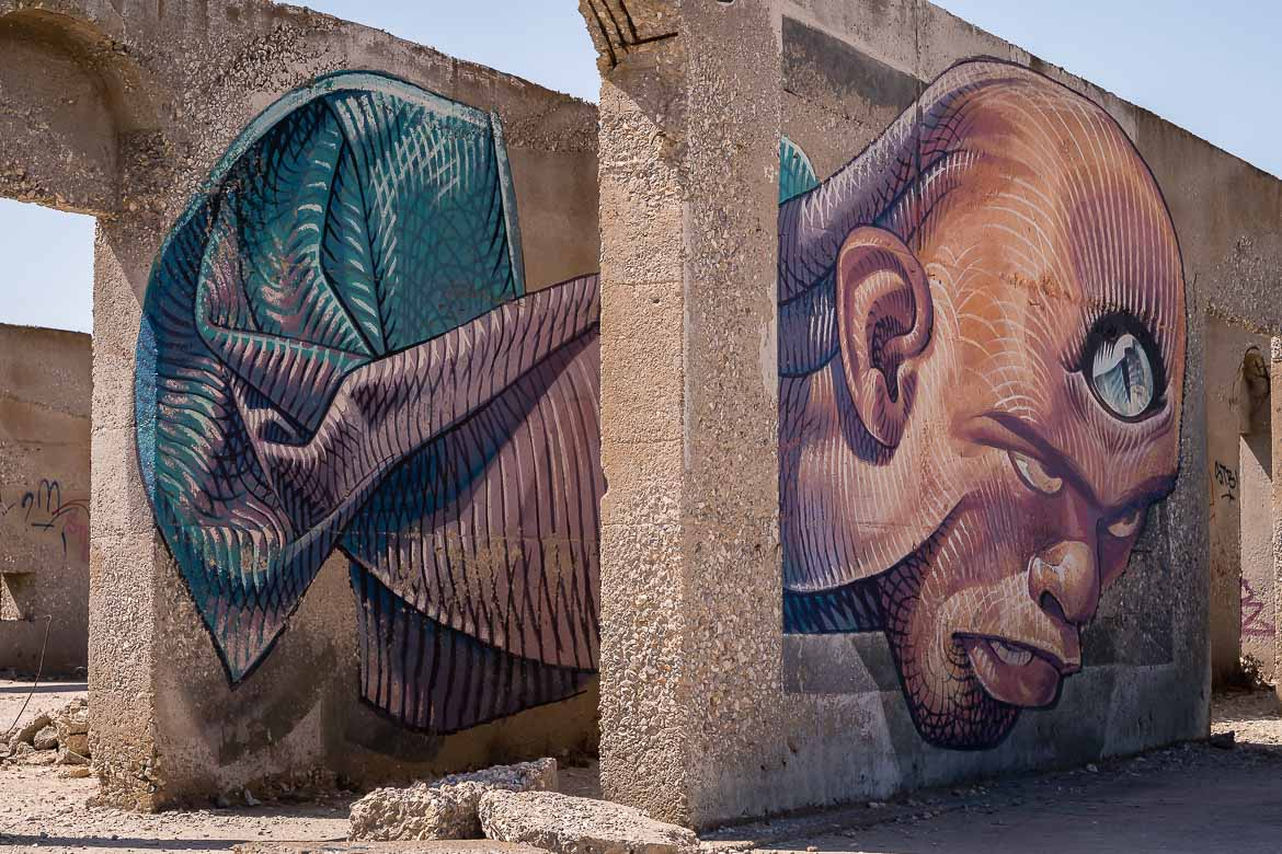 """This image shows a street art mural of WD at an abandoned hotel in Aliko Naxos. The mural's name is """"The third eye"""" and it shows a man with an eye on his forehead. If you're wondering what to do in Naxos, checking out the amazing street art should be at the top of your list."""