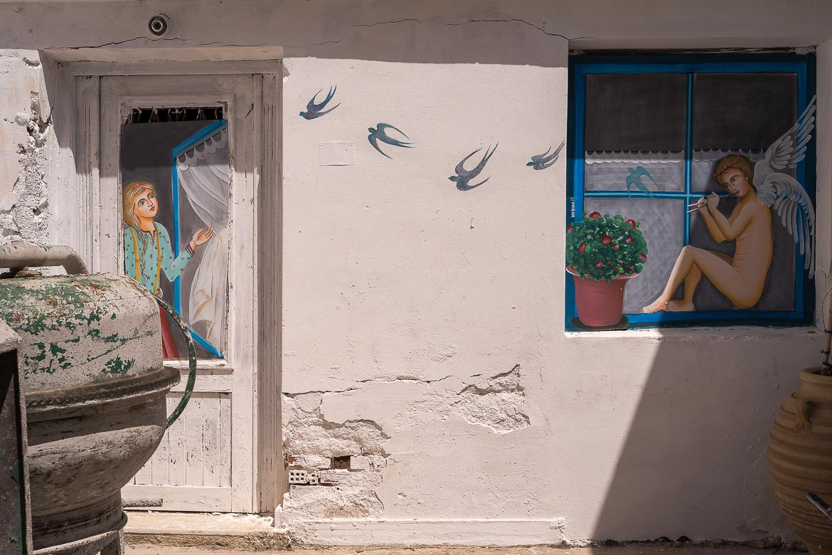 This image shows an artwork displayed on the facade of a house in Chora. On the left side there is a woman displayed on the door who is looking to an angel displayed on the window at the right side of the wall.