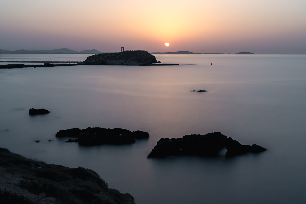 This image shows Portara during sunset. The photo is taken from Grotta and the sea is smooth and calm.