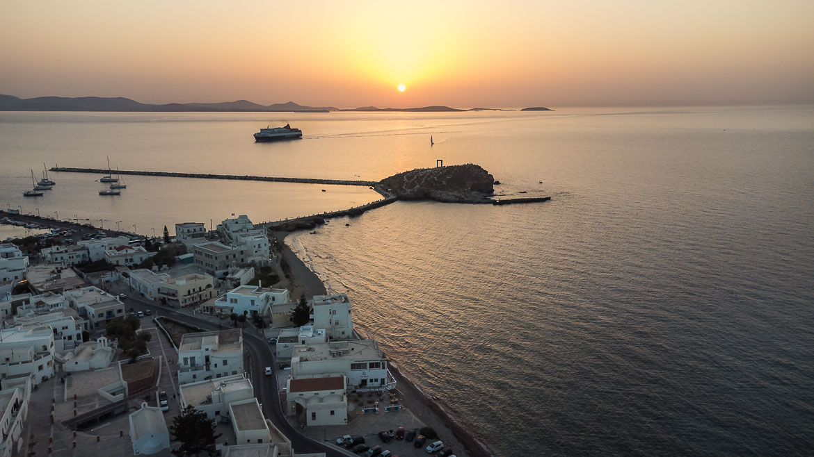 This image shows Portara and a ferry approaching Naxos port during sunset. The photo is taken from a drone.