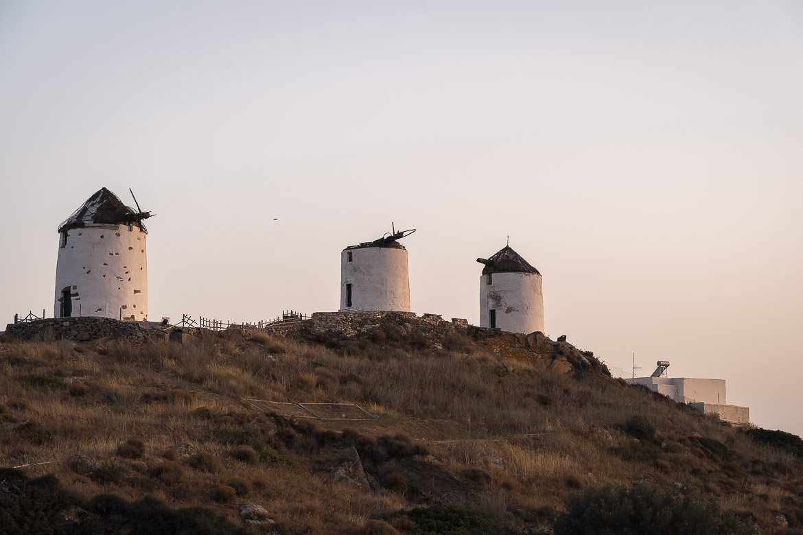 This image shows three windmills in Vivlos village at sunset.