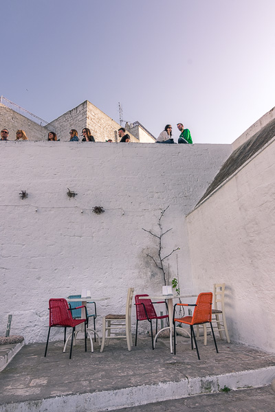 This image shows colourful chairs of a bar in Ostuni. They make a wonderful contrast with the blindingly white wall.