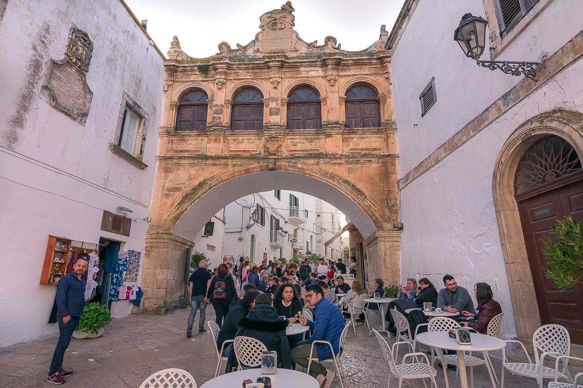 This photo shows the Arco di Scoppa. This is a wonderful architectural element that resembles a covered bridge. Its golden colour stands out compared to the two white buildings it connects.