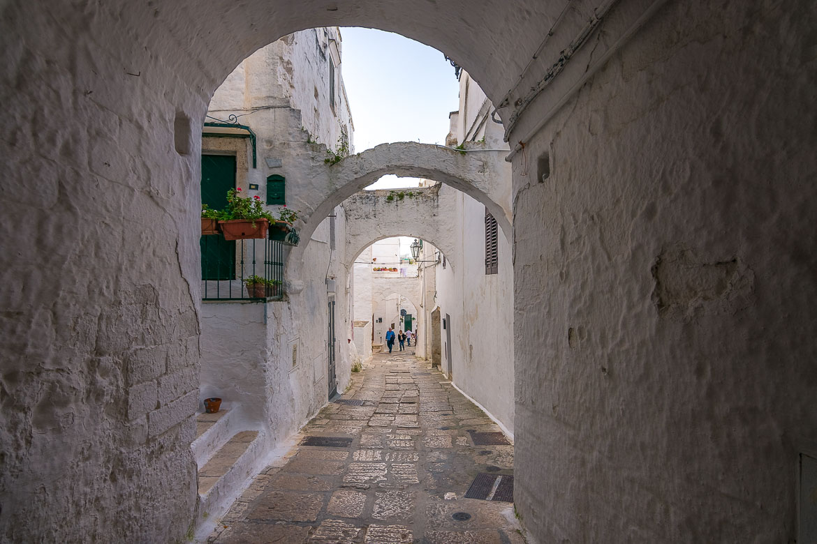 This image shows a quaint narrow alley in Ostuni Old Town. All buildings are white. They are connected by stone arches.
