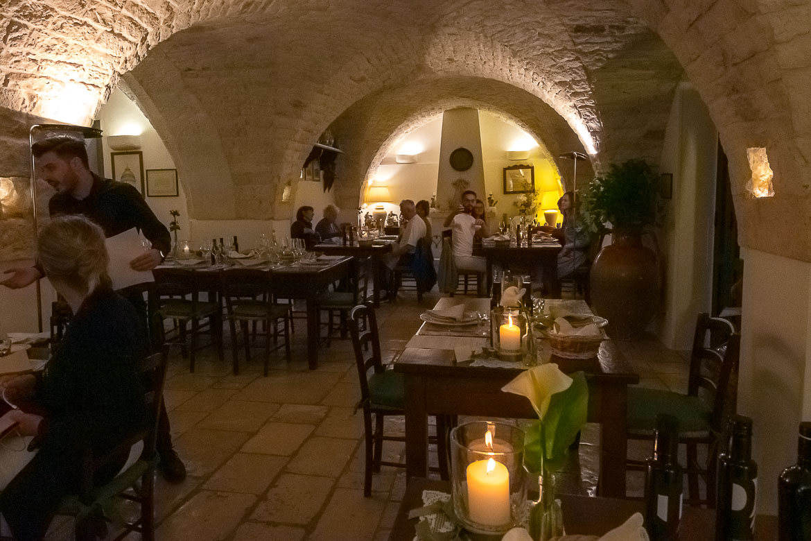 This photo shows the interior of the masseria restaurant. It's dimly lit in a way that showcases the gorgeous vaulted ceiling.