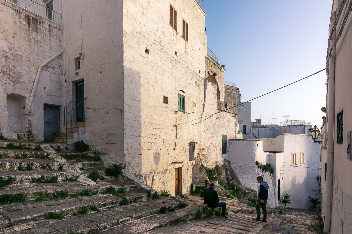 This photo shows two men as they stop to take in the beauty of Ostuni Old Town.