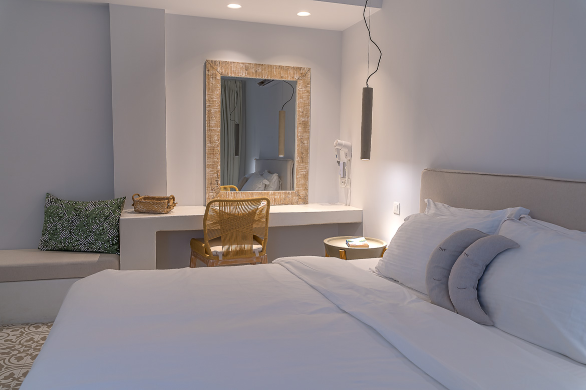 This image shows the interior of the room we stayed at Adonis Hotel. The room is smartly decorated with white linen and light brown details.
