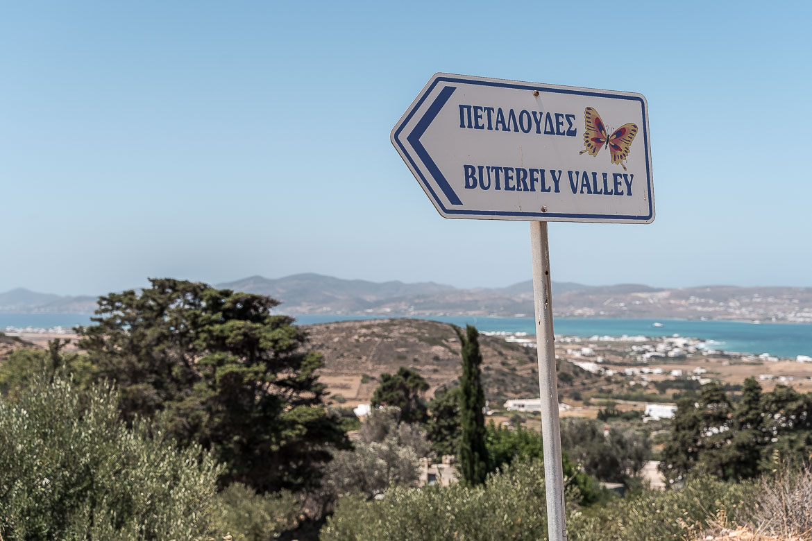 This is a road sign pointing to the valley of the butterflies. In the background, there is a panoramic view of Antiparos.