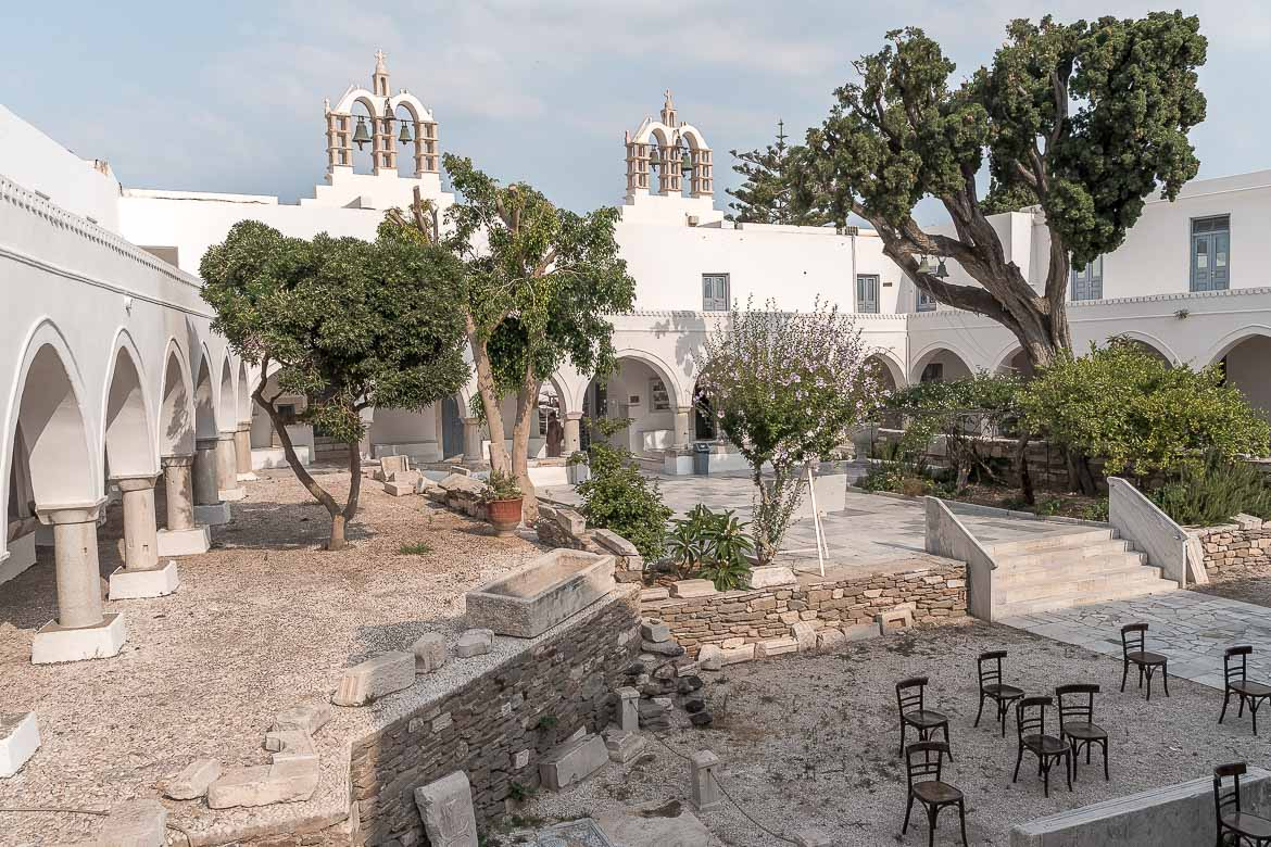 This is a panoramic shot of the glorious inner courtyard at Panagia Ekatontapiliani Church in Parikia. There are trees and chairs and the image evokes a tranquil ambience. If you're wondering what to do in Paros Greece, a visit to Ekatontapiliani Church is a definite must.