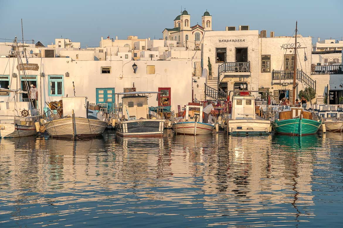 This is a panoramic shot of the Old Port in Naoussa at sunset. There are many traditional boats which reflect on the calm sea water. In the background, the whitewashed buildings of Naoussa. We believe that this photo is very characteristic of Paros and this is why we chose it as the featured image for our article on what to do in Paros Greece.