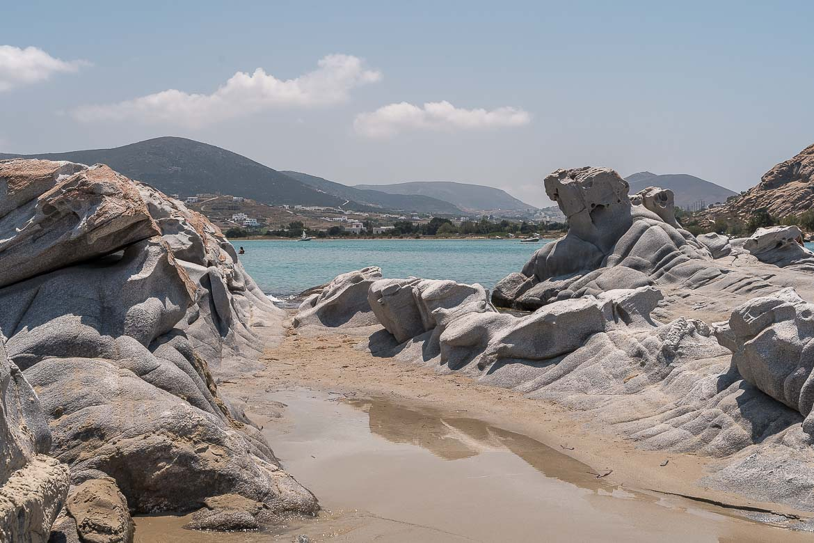 This image shows the grey rock formations at Kolymbithres Beach. The sand is golden and the sea is light blue. Having a swim at Kolymbithres is one of the best things to do in Paros.