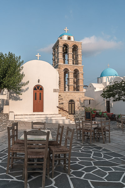 This image shows the central square of Kostos Village. There is a white church with a brown bell tower and several tables and chairs scattered around.