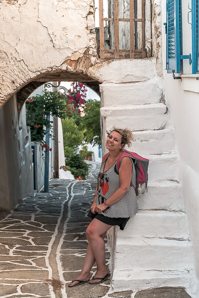 This image shows Maria leaning at some gorgeous whitewashed steps and smiling to the camera.
