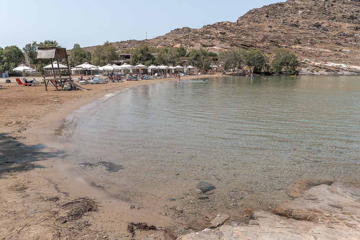 This is a panoramic shot of Monastiri Beach, a sheltered bay of shallow emerald waters with sunbeds and umbrellas.