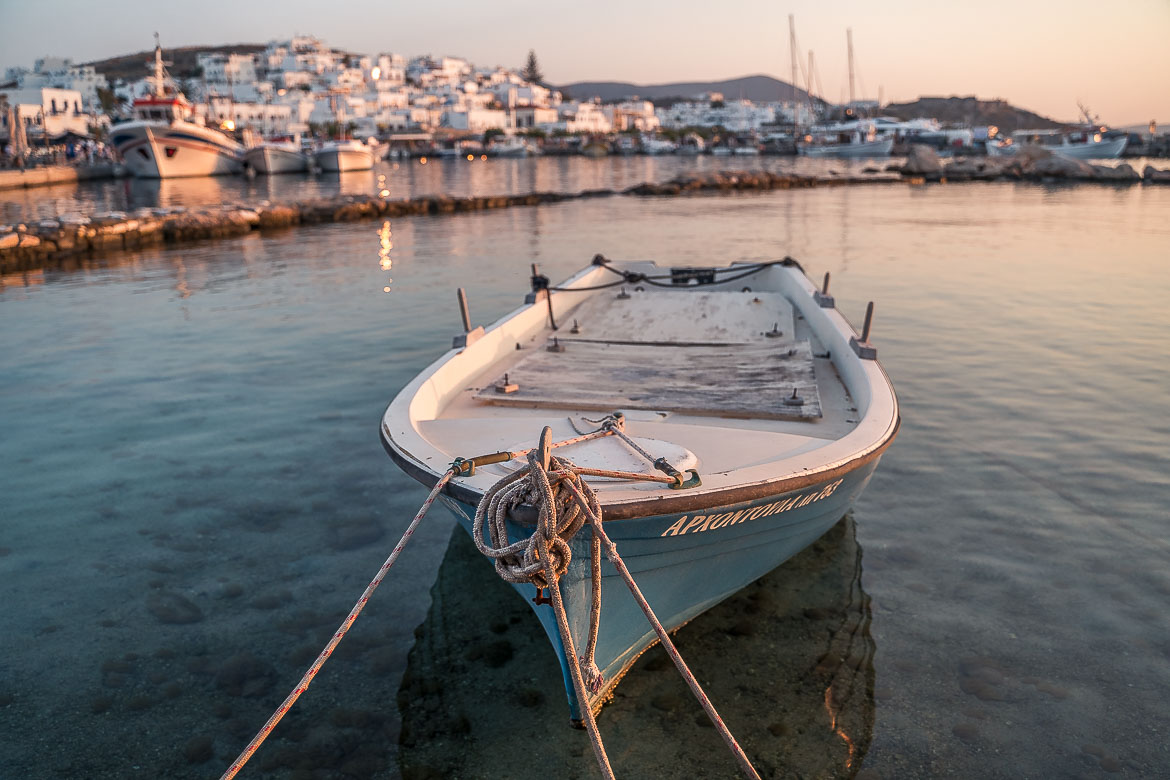 This is a close up of a traditional boat in Naoussa Old Port. In the background, the whitewashed buildings of Naoussa are painted gold as the sun sets.