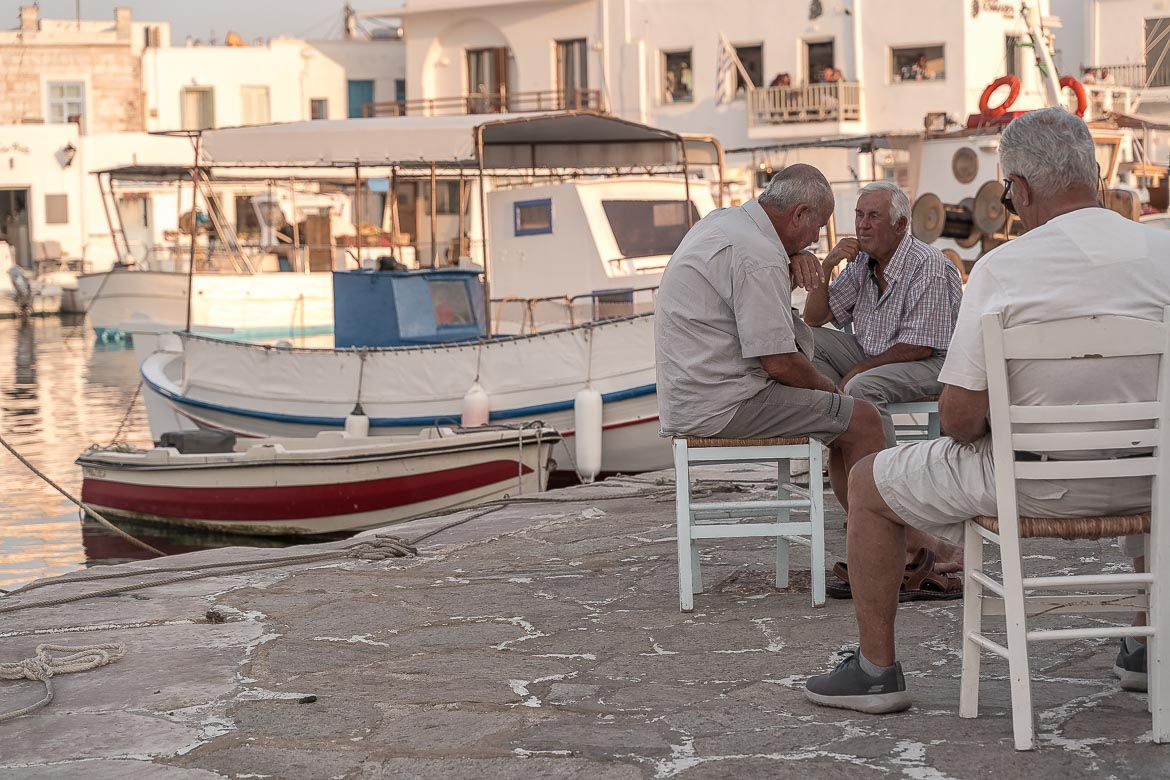 This image shows three locals chatting casually at the Old Port of Naoussa.