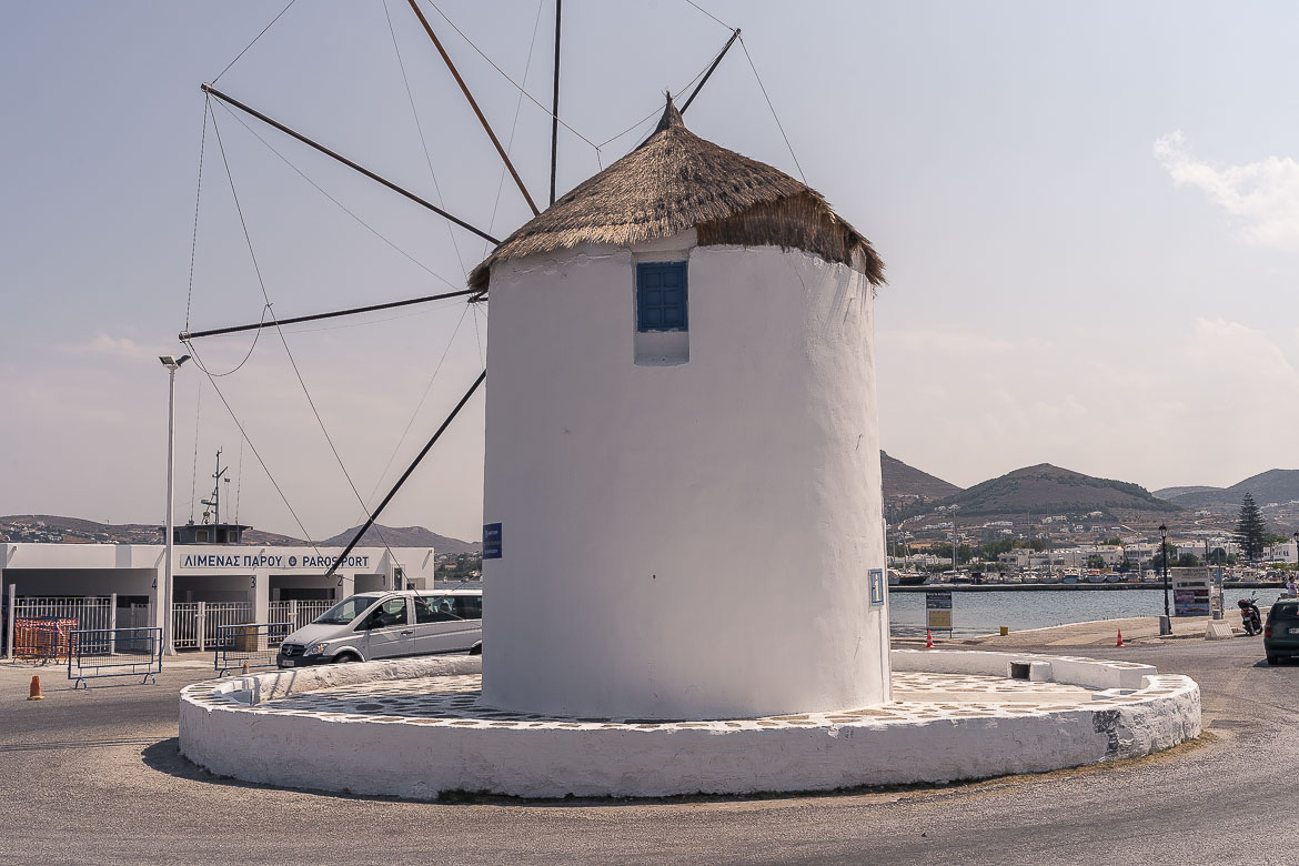 This is a close up of a white windmill which is located just outside the main building of Parikia Port.
