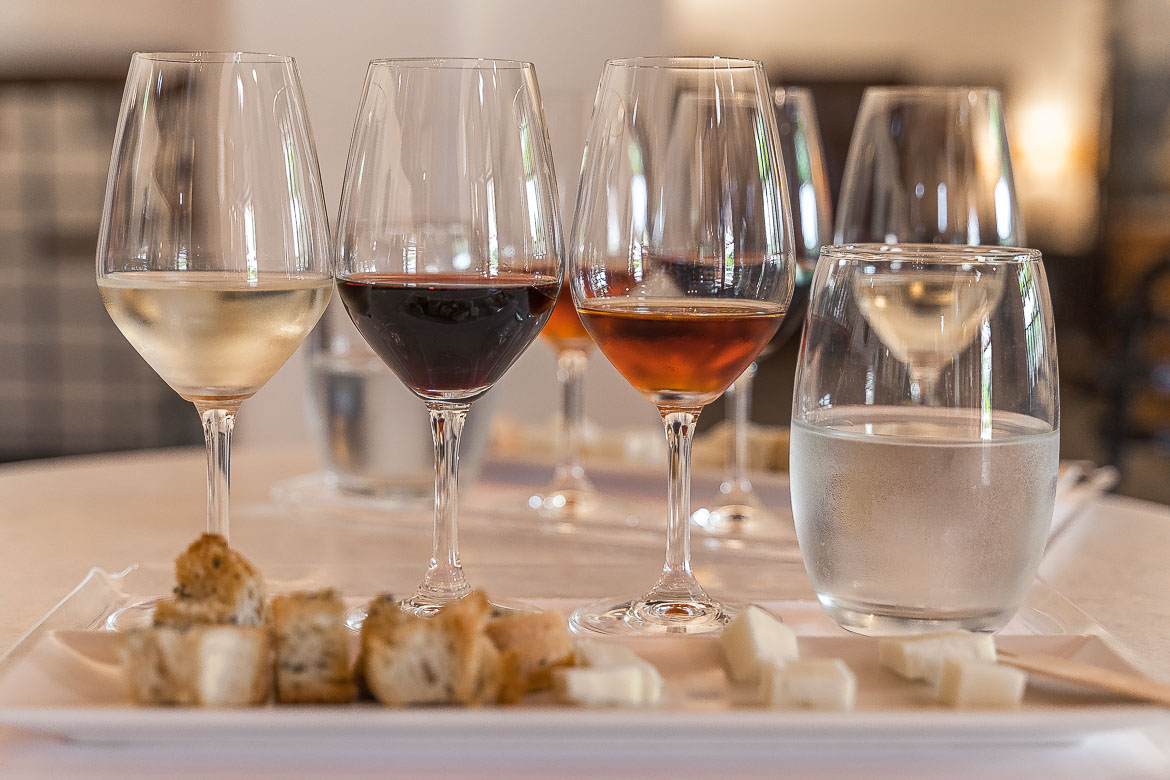 This is a close up of three glasses of wine each of which contains a sample of the island's three DOC wines. There's also a plate with cheese and bread and a glass of water.