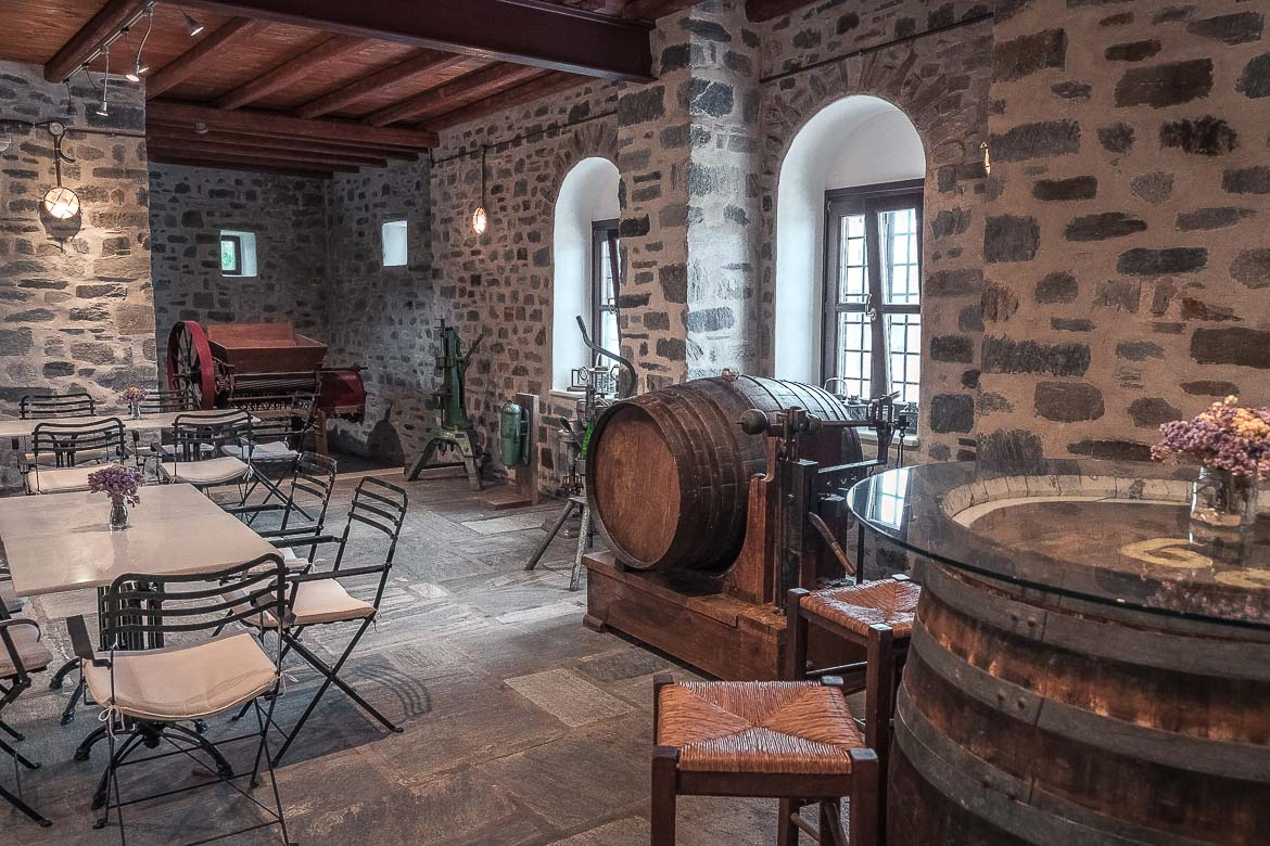 This image shows a room inside Moraitis Winery. There are barrels of wine and tables and chairs.