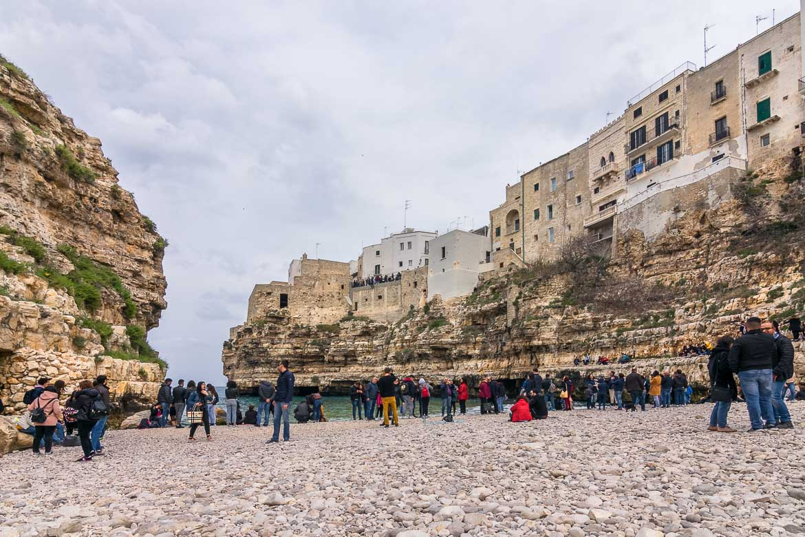 This photo was taken from Lama Monachile Beach. There are many people on the beach. Nobody's swimming because it's a cold and cloudy spring day. The Old Town looms above the beach as it sits atop a dramatic limestone cliff.