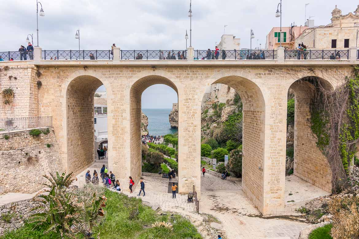 This photo shows the impressive Lama Monachile Bridge. It is a bridge with tall arches. There are people walking along the bridge. You have to walk below the bridge to get to Lama Monachile Beach. The latter is visible in the background.