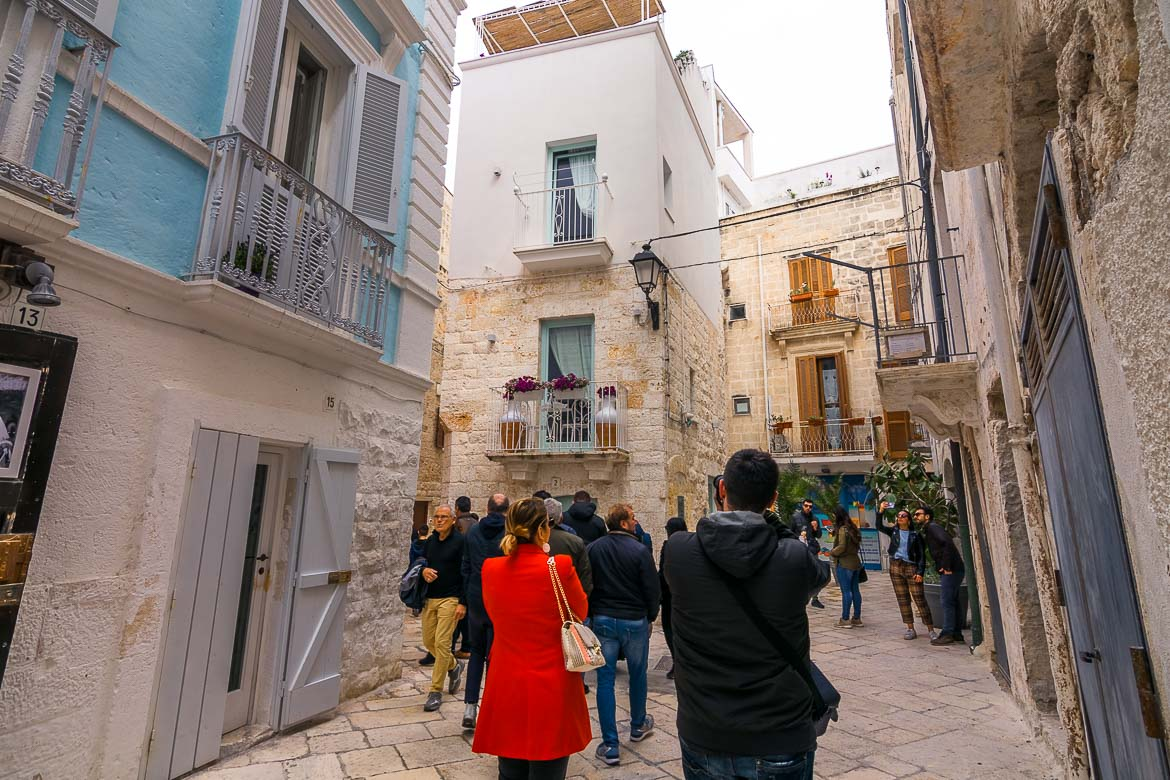 This photo shows crowds of people walking along a narrow street in the Old town.