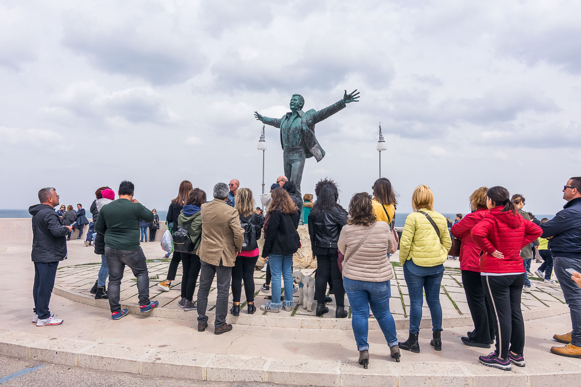This image shows the statue of Domenico Modugno. The statue is surrounded by many people who stand to admire it.